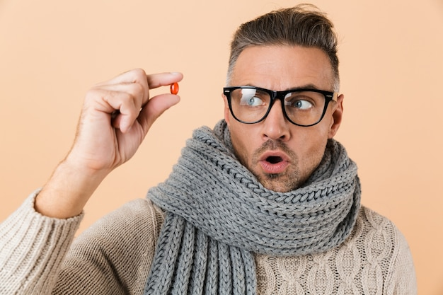 Close up portrait of a shocked man dressed in sweater and scarf standing isolated over beige wall, showing pill capsule