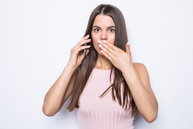 Close up ritratto di donna scioccata a parlare con qualcuno al telefono sul muro bianco.
