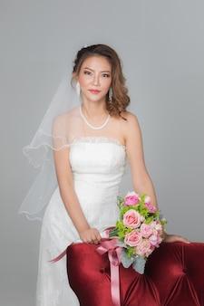 아름다운 아시아 신부가 서서 꽃다발을 들고 회색 검정색 배경에 있는 빨간 의자에 손을 얹은 미소의 초상화를 클로즈업합니다.