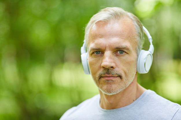 カメラを見ているヘッドフォンを身に着けているスポーティなハンサムな成熟した大人の男性のクローズアップポートレートショット