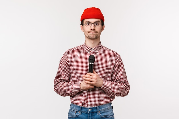 Close-up portrait of shy and geeky cute young bearded guy in glasses and red beanie