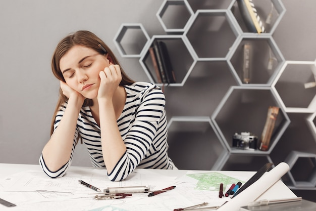 Close up portrait of sleepy charming young european freelance engineer girl fall asleep on working place during preparations to meeting with team leader to talk about work mistakes