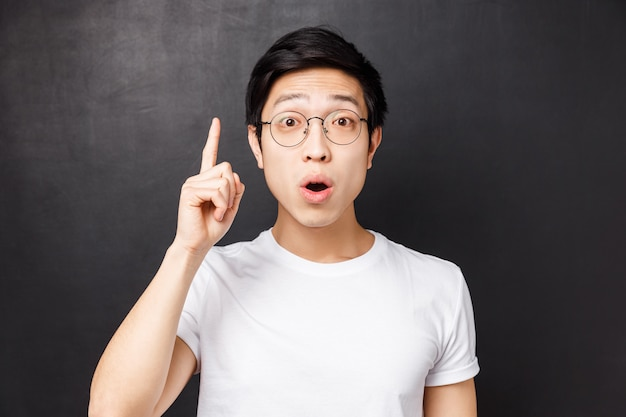 Close-up portrait of smart and creative asian man in glasses, raising index finger add suggestion, saying his opinion or thought, want to ask question, invented good plan,