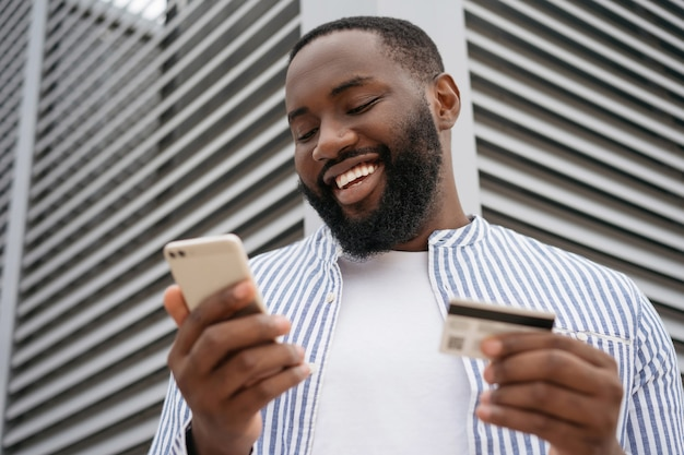 Close up portrait of smiling african man holding credit card, using modern mobile app shopping online