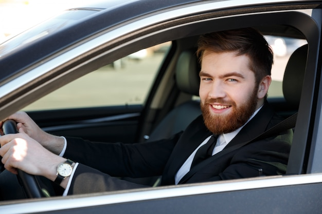 Close up portrait of a smiling bearded man in suit driving car