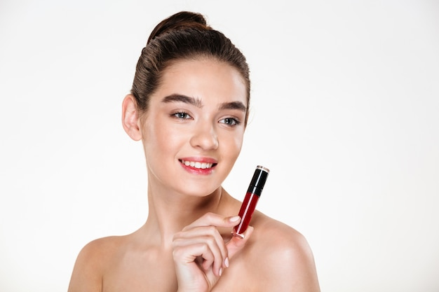 Close up portrait of smiling brunette woman wearing makeup holding lip gloss at her face and looking aside