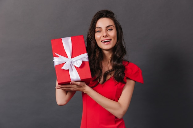 Close-up portrait of smiling dark-haired woman holding decorated box with gift. lady in red is smiling sincerely on black background.