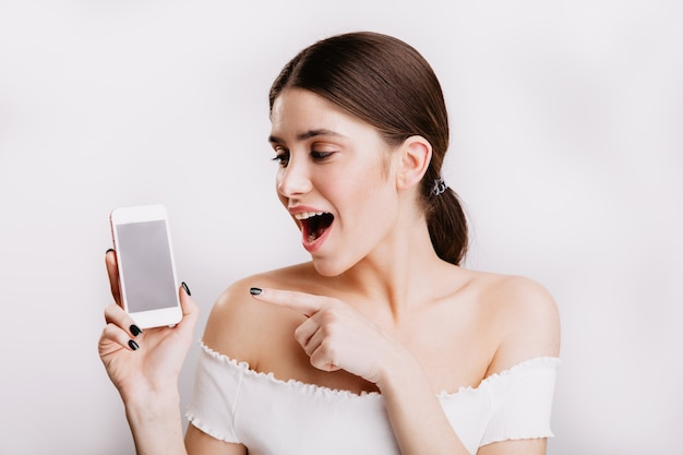 Close-up portrait of smiling dark-haired woman in white top, looking at phone in amazement.