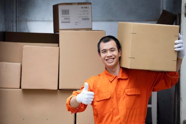 Chiuda sul ritratto dell'uomo di consegna sorridente che mostra segno giusto