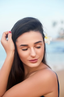 Close up portrait of smiling female by the sea with flower in her hair