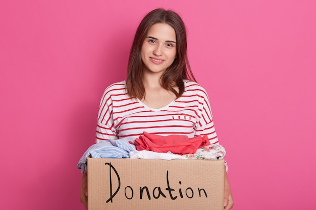 Close up portrait of smiling girl volunteering holding paper box with clothes for poor people, lady making donation