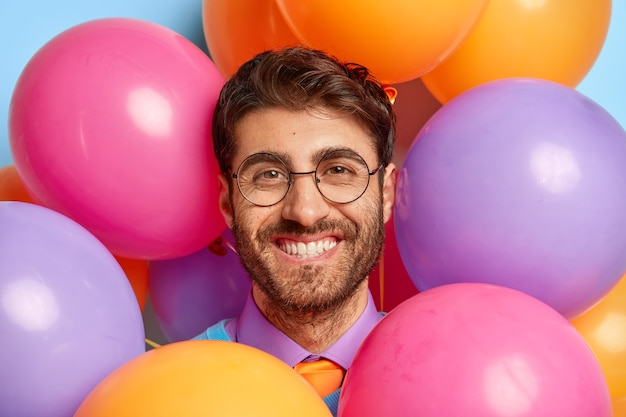 Close up portrait of smiling guy surrounded by party balloons posing