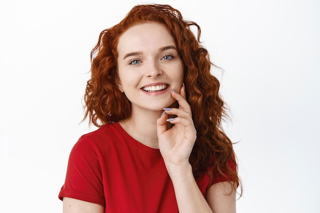 Close up portrait of smiling happy woman with ginger curly hair, touching pale smooth and healthy skin with fingertips, looking cheerful and laughing, white wall