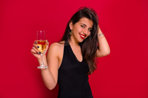 Close-up portrait of smiling happy woman with long dark hair posing with a glass of champagne over isolated red background