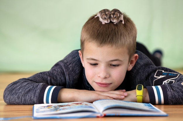 Close up portrait of smiling little boy reading book with small pet hamsters