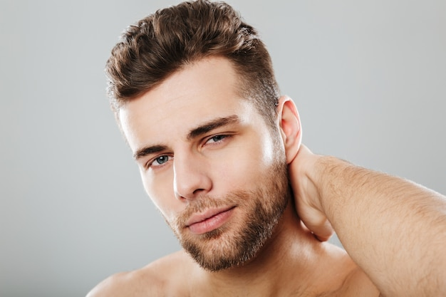 Close up portrait of a smiling man combing his hair