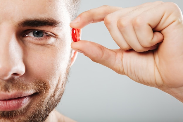 Close up portrait of a smiling man holding red capsule