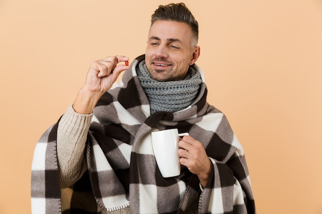Close up portrait of a smiling man wrapped in a blanket standing isolated over beige wall, showing pill capsule