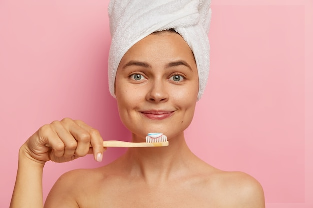Close up portrait of smiling optimistic woman with fresh skin, holds toothbrush with toothpaste, wears white towel on head, looks directly, has oral hygiene procedure