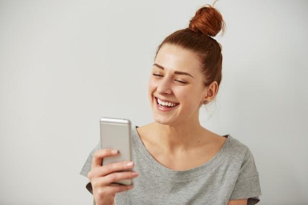 電話を見て笑顔や笑いの若いフリーランサーの女性の肖像画を閉じる