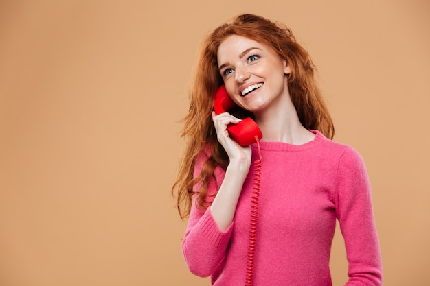 Close up portrait of a smiling pretty redhead girl talking by classic red phone