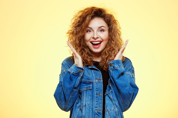 Close up portrait of smiling surprised beautiful brunette curly girl in casual street jeans jacket over yellow wall