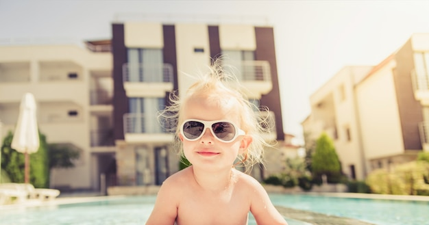 The close up portrait of a smiling toddler girl, getting out of swimming pool.