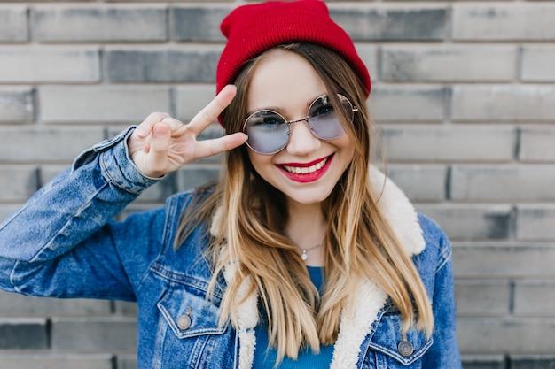 Ritratto del primo piano della ragazza meravigliosa sorridente che gode della buona giornata in primavera. colpo all'aperto di spettacolare signora in abiti casual in posa con piacere sul muro di mattoni.