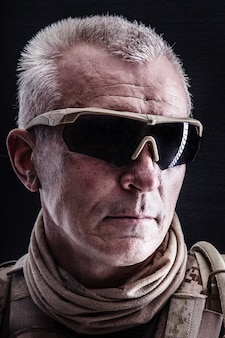 Close up portrait of special forces white-haired veteran in field uniforms, black