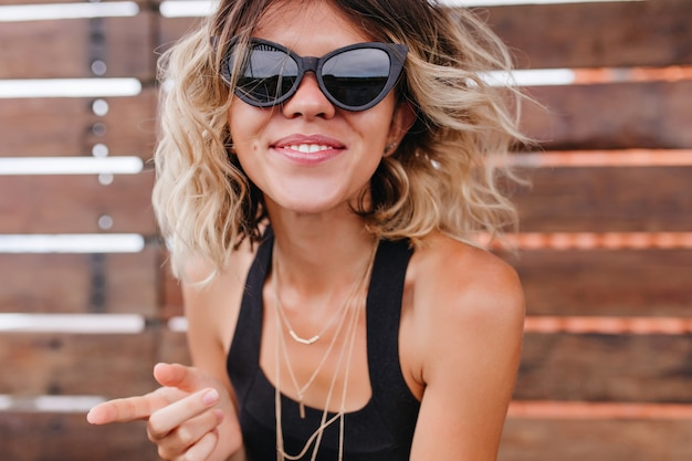 Close-up portrait of spectacular young woman posing in black sunglasses. fascinating short-haired girl isolated on wooden wall.