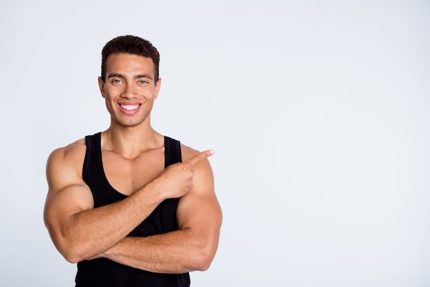 Close-up portrait of sportive muscular guy show copy place space ad isolated over gray background Premium Photo