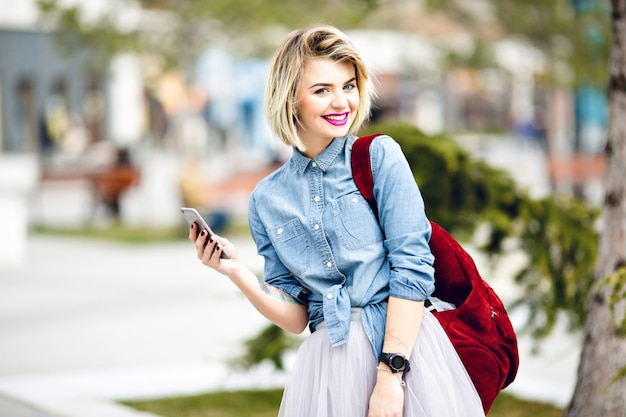 A close-up portrait of a standing smiling girl with short blond hair and bright pink lips hoding a smartphone