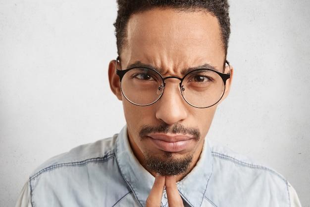 Close up ritratto di rigoroso capo maschio serio, indossa grandi occhiali rotondi