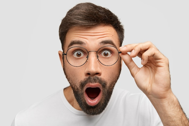 Close up portrait of stunned bearded young guy drops jaw, has bugged dark eyes, sees something unbelievable and surprising, has eyewear, isolated on white wall. people, emotions concept