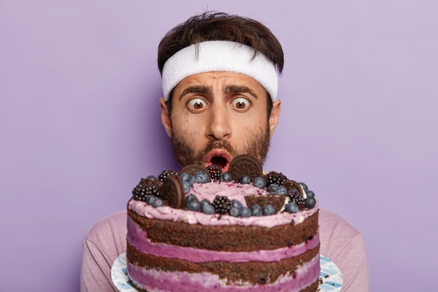 Close up portrait of stupefied man stares with bugged eyes at delicious sweet cake, has big desire to eat tasty dessert, keeps to diet and goes in for sport, wears white headband