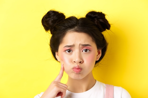 Close-up portrait of stylish asian girl with bright makeup and glowing skin, pouting and frowning, poking her cheek with sad face, standing upset on yellow