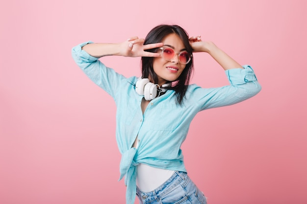Close-up portrait of stylish asian young woman wears elegant glasses and cotton shirt. adorable hispanic girl with black shiny hair relaxing in pink room.