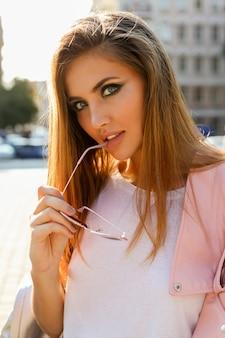 Chiuda sul ritratto della femmina europea bionda alla moda in giacca di pelle rosa in posa all'aperto.