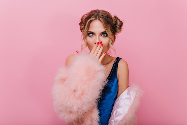 Close-up portrait of stylish girl in fur coat, standing on pink background with surprised face expression. fair-haired young woman with red manicure shyly covers her mouth with palm