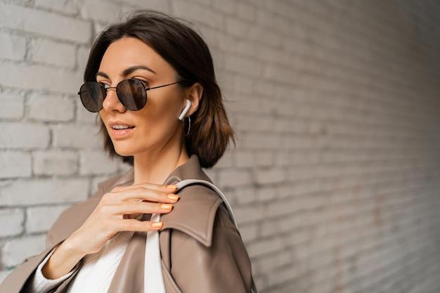 Ritratto ravvicinato di una donna elegante dai capelli corti con un cappotto di pelle casual e occhiali da sole in posa su un muro di mattoni urbano