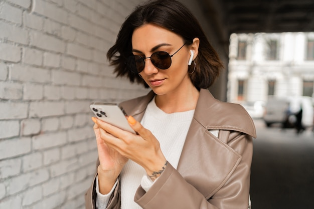 Close up ritratto di elegante donna dai capelli corti con gli auricolari in cappotto di pelle casual e occhiali da sole utilizzando smartphone e posa sopra il muro di mattoni urbano