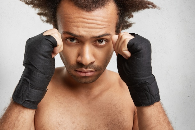 Close up portrait of successful male boxer shows strong arms and clenched fists wrapped by protective bandages