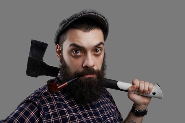 Close up ritratto di barba uomo sorpreso tubo di fumo e tenere l'ascia in mano tatuata. ritratto maschile forte e serio isolato su sfondo grigio.