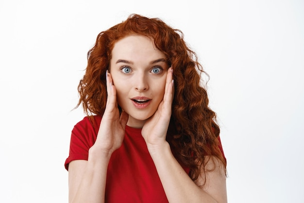 Close-up portrait of surprised ginger girl receive amazing news, look with hopeful face and slight disbelief, open mouth and raise eyebrows amazed, white wall