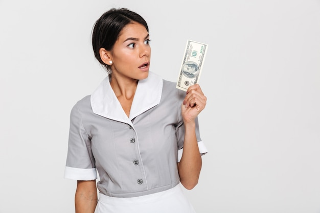 Close-up portrait of surprised young woman in uniform holding hundred dollar banknote