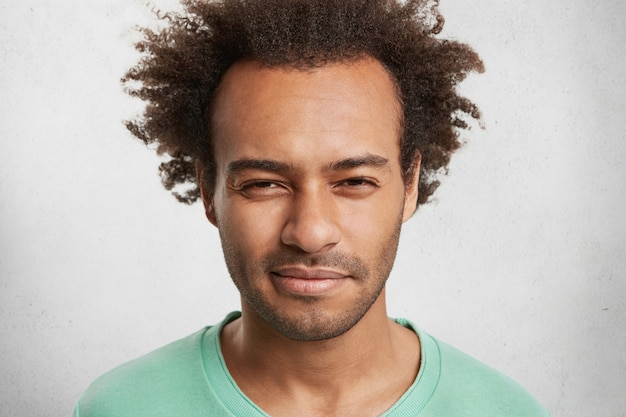 Close up portrait of suspicious dark skinned man wears green sweater, has serious expression