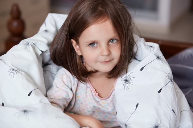 Close up portrait of sweet little dark haired girl sitting in her bed and wrapped white blanket, looking at camera and smiling while being at home in cosy room, female kid wearing white pajama.