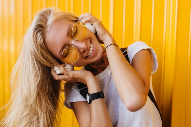 Close-up portrait of tanned charming woman listening music with eyes closed on yellow