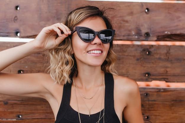 Ritratto del primo piano di giovane donna abbronzata in occhiali da sole alla moda. ragazza affascinante che tocca i suoi occhiali e che sorride.