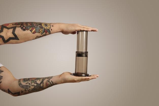 Chiuda sul ritratto delle mani dell'uomo tatuato che stringe un aeropress vuoto sul muro grigio chiaro